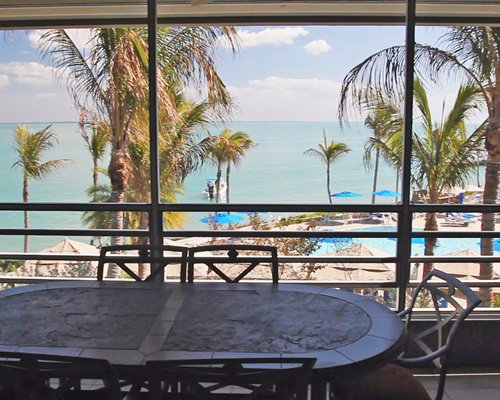 Balcony view of the ocean with patio furniture.