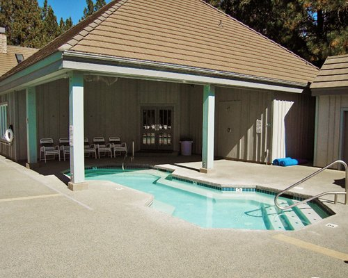 An outdoor swimming pool with patio furniture and resort units.