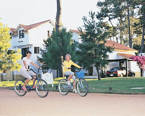 Two people cycling on a pathway alongside the resort.