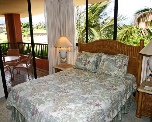 A well furnished bedroom with a queen bed and balcony.