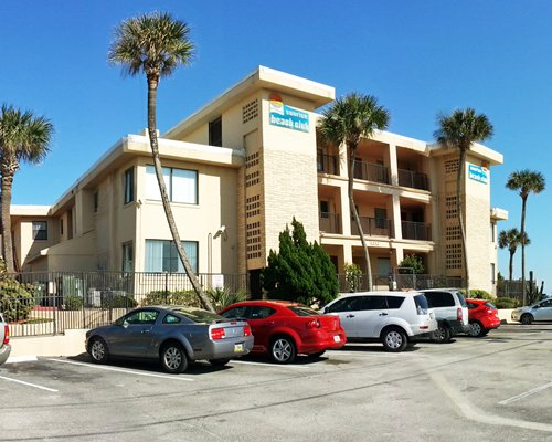 A street view of multi story resort units with the parking lot.