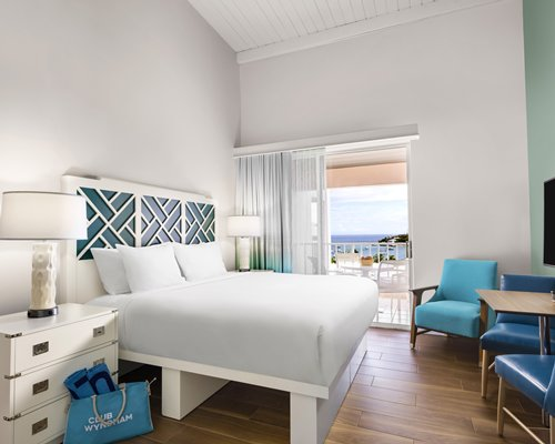 A well furnished living room with a television spiral stairway dining area and balcony.