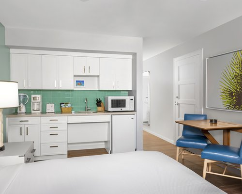 A well equipped kitchen with a dining table alongside the stairway.
