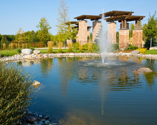 Scenic picnic area with a pond and fountain.