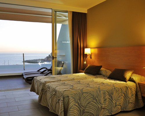 A well furnished bedroom with balcony chaise lounge chairs and ocean view.