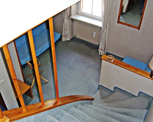 An aerial view of a living room alongside the wooden staircase.