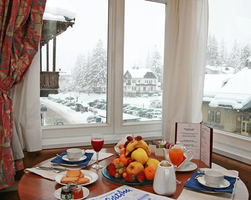 A view of various food items on the dining table with an outside view.