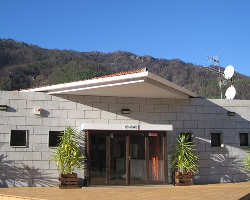 An exterior view of the resort alongside mountains.