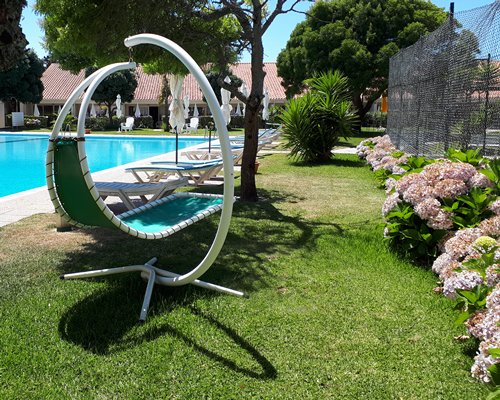 An outdoor swimming pool with chaise lounge chair.