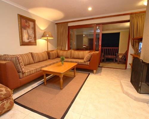 A well furnished living room with a television balcony and patio furniture.