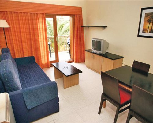 A well furnished living room with a dining area television and balcony.
