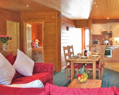 An open plan well furnished living room with a wooden dining and kitchen area.