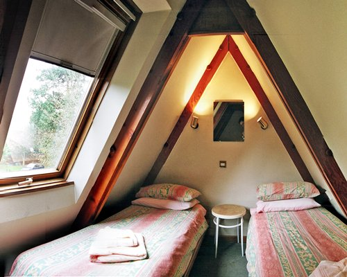 A furnished bedroom with two beds and an outside view.