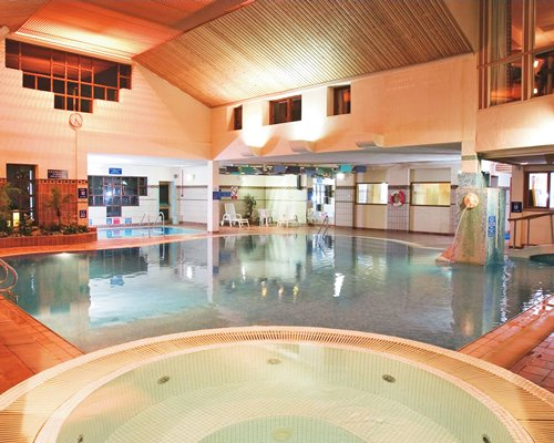 An indoor swimming pool with hot tub and chaise lounge chair.