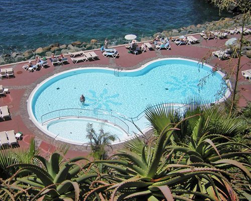 An aerial view of an outdoor swimming pool with chaise lounge chair alongside the ocean.