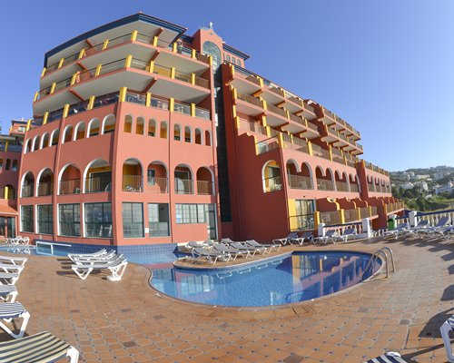 Exterior view of Royal Orchid with outdoor swimming pool and chaise lounge chairs.