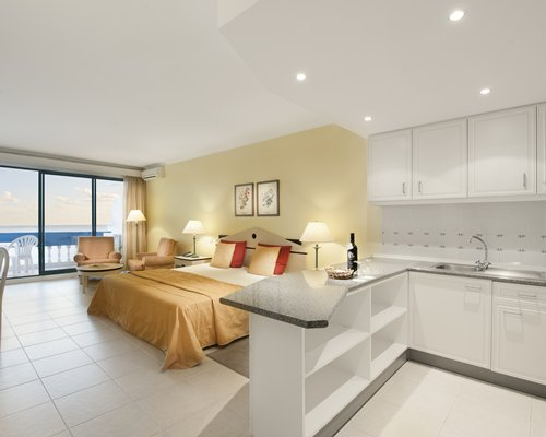 A well furnished bedroom with open plan kitchen balcony and ocean view.