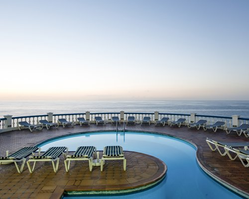 Outdoor swimming pool with chaise lounge chairs and ocean view.