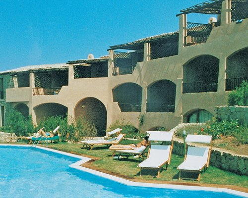 An outdoor swimming pool with chaise lounge chairs alongside the hotel.