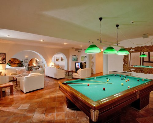 A recreational room with pool table and television.
