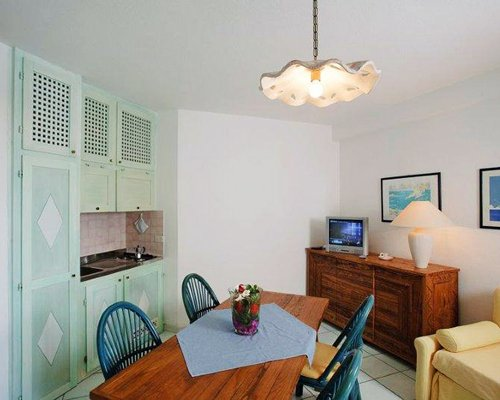 Furnished living room with open plan kitchen dining are and television.