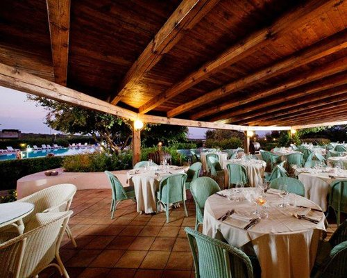 An outdoor fine dining area alongside swimming pool.