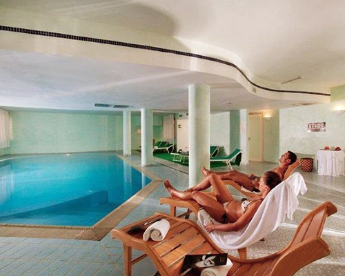 A couple relaxing on chaise lounge chairs alongside an indoor swimming pool.