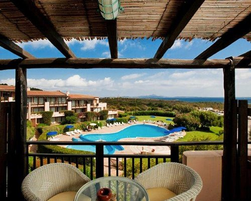 Scenic view of outdoor swimming pool from the balcony with patio chairs.