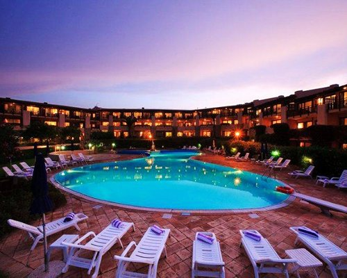 An outdoor swimming pool with chaise lounge chairs alongside multi story resort condos at dusk.