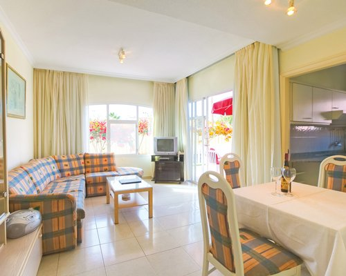 A well furnished living room with a dining area open plan kitchen television and outside view.