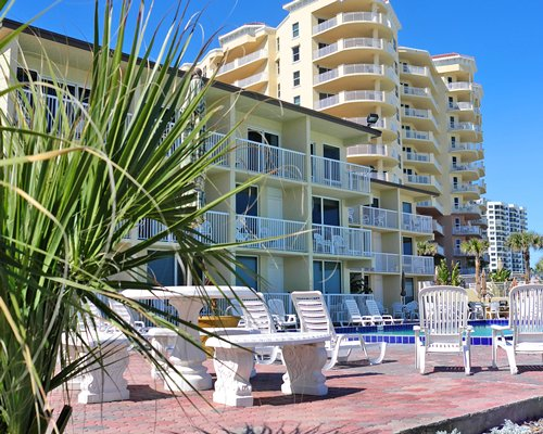 Exterior view of multiple unit balconies with outdoor swimming pool and chaise lounge chairs.