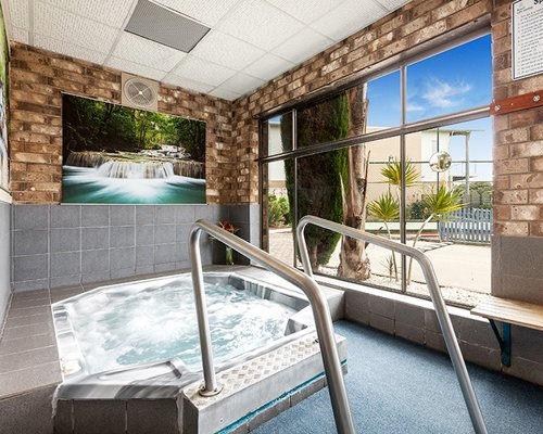 A view of an indoor hot tub with an outside view.