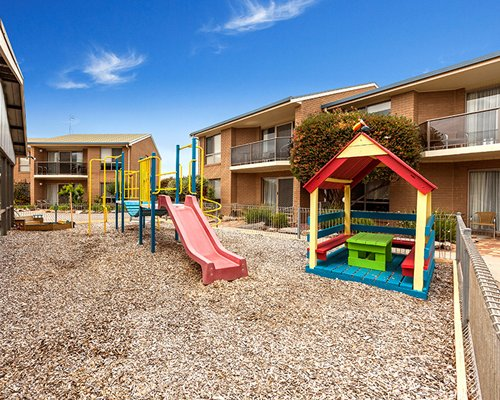 An outdoor playscape alongside resort units.