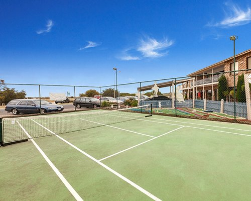 Outdoor recreation area with a tennis court and parking lot.