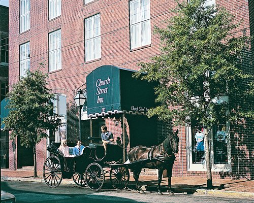 An exterior view of the Church Street Inn alongside a horse carriage.