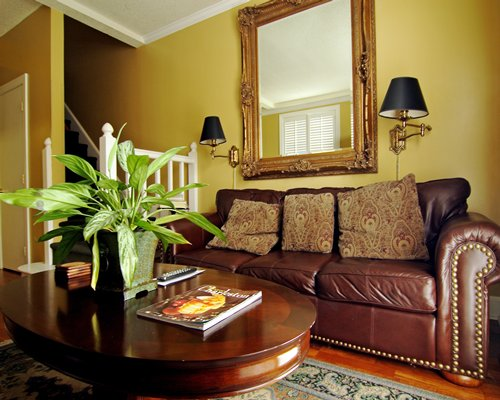 A well furnished living room with double pull out sofa and a mirror.