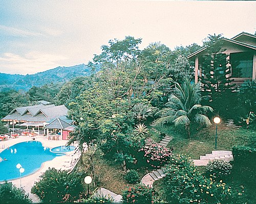 Exterior view of an outdoor swimming pool surrounded by wooded area.