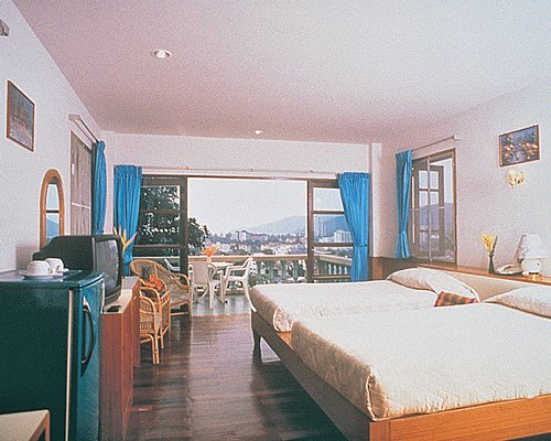A well furnished bedroom with two beds television refrigerator and a patio.