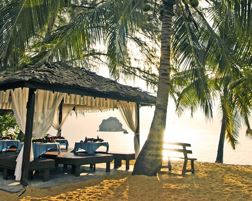 An outdoor fine dining area with coconut trees alongside a water view.