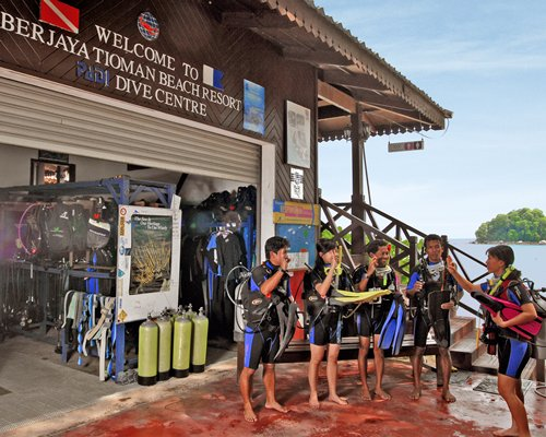 A group of people standing before the beach resort dive center.