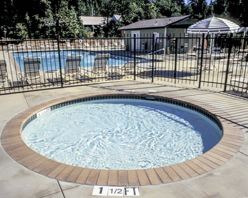 Outdoor hot tub alongside swimming pool with chaise lounge chairs and sunshade surrounded by wooded area.