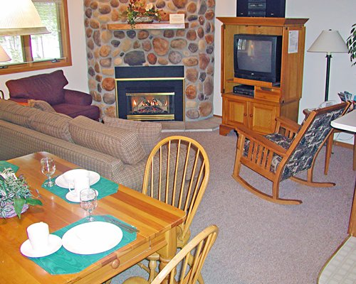 A well furnished living room with a dining area television and fire in the fireplace.