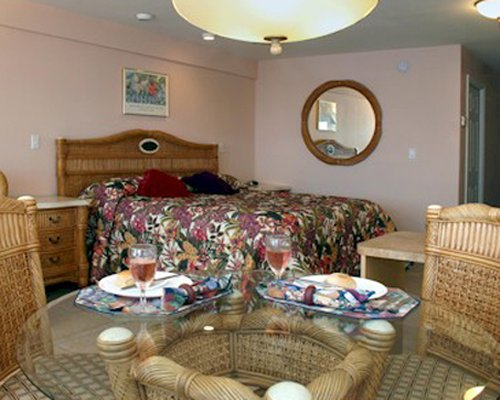 A well furnished bedroom with a queen bed and dining area.