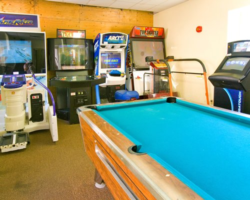 An indoor recreational room with a pool table and arcade game.