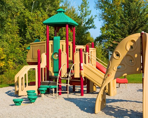 An outdoor playscape surrounded by trees.
