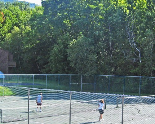 People playing tennis in an outdoor tennis court.
