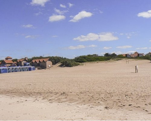An exterior view of a large outdoor recreational area covered in sand.