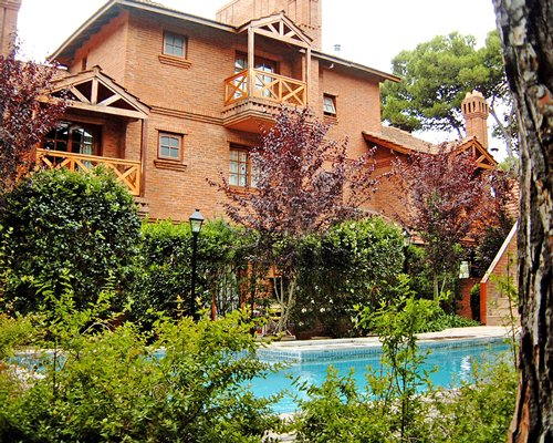 Outdoor swimming pool alongside a unit with balcony.