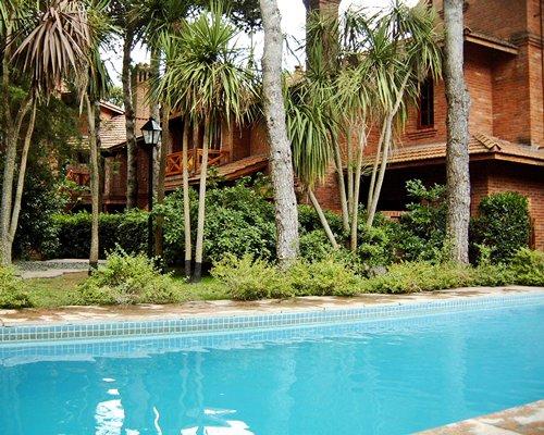 An outdoor swimming pool alongside multi story resort units.