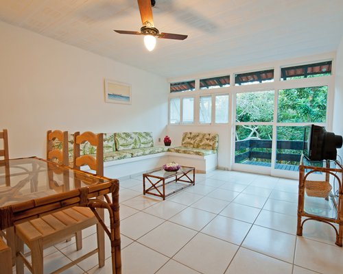 A well furnished living room with television and glass top dining table alongside the balcony.